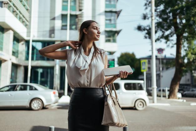 女性は建物とバッグとタブレットpcを運ぶ