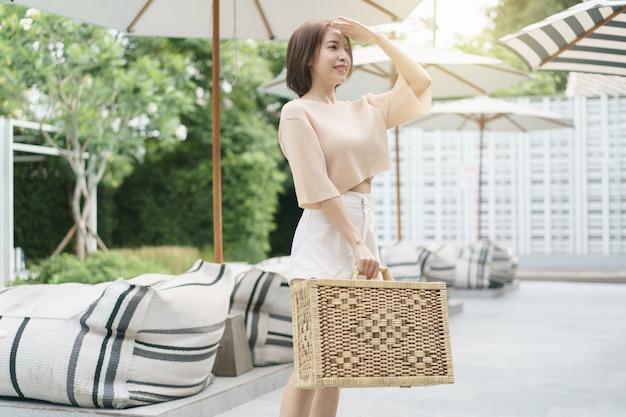 女性は籐のスーツケースを運ぶ。