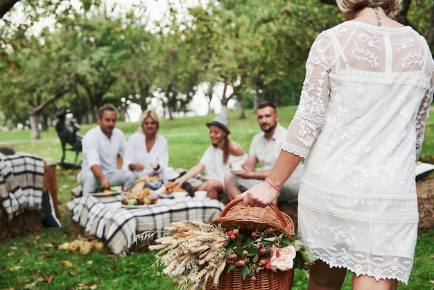 Женщина несет корзину с сухими растениями. группа взрослых друзей отдыхает и беседует во дворе ресторана во время обеда