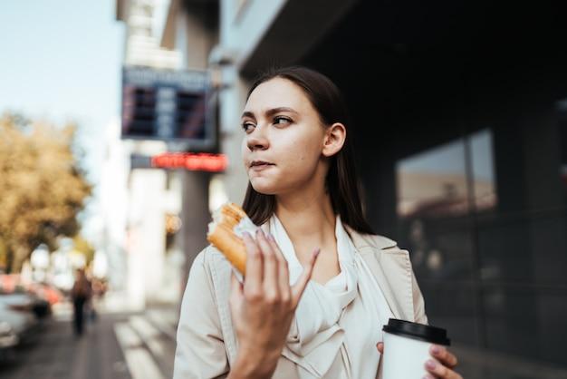 女性は彼女の手でコーヒーを運び、建物とパイを持っています