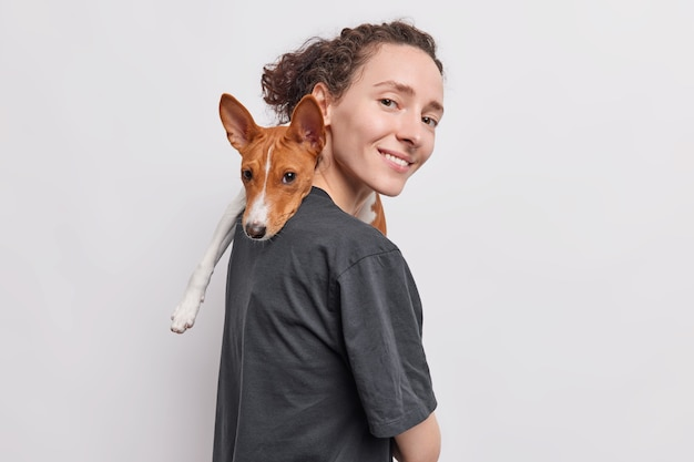 Woman carries dog on shoulder plays with favorite pet expresses love and care stands sideways isolated over white