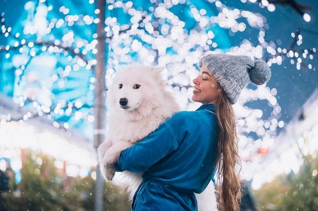 여자는 그녀의 팔에 그녀의 개를 운반
