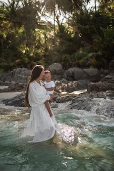女性は海で彼女の腕に息子を運ぶ
