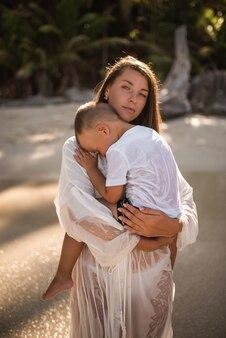 Женщина несет сына на руках в море