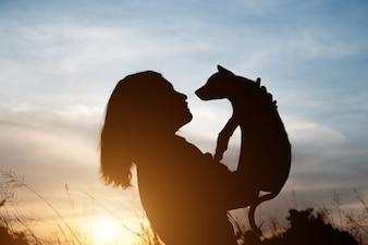 Woman carry her pet and hugging up to the sky.
