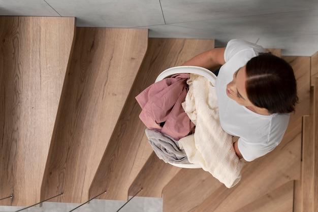 바구니에 더러운 옷을 잔뜩 들고 있는 여자