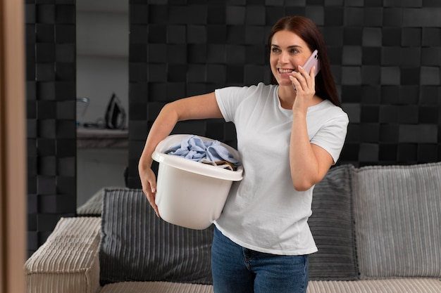 かごの中に汚れた服の束を運ぶ女性