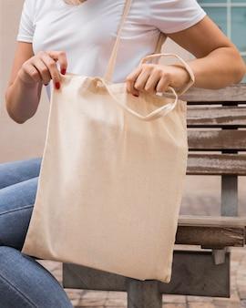 ミディアムショットの生地バッグを運ぶ女性