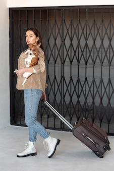 Женщина несет багаж и держит ее собаку