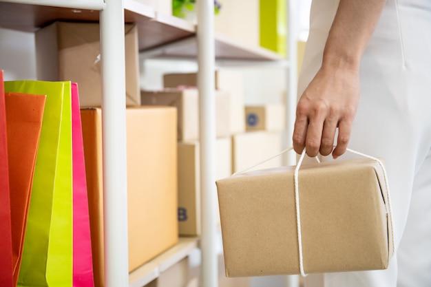 Женщина нося почтовый конец коробки вверх, современные онлайн покупки и концепцию электронной коммерции.