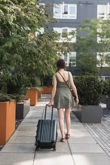 都市公園でスーツケースを運ぶ女性