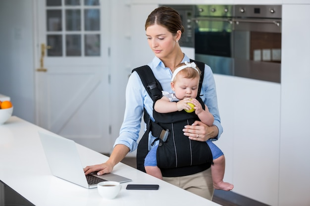 Woman carrying baby girl while using laptop at table