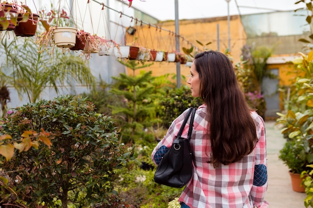 Woman carrying bag in greenhouse