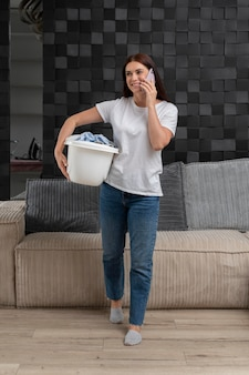 Woman carrying a bunch of dirty clothes in the basket