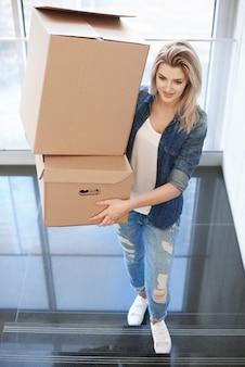Женщина, несущая картонную коробку наверху