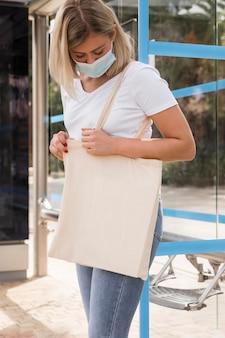 Donna che porta una vista laterale della borsa in tessuto