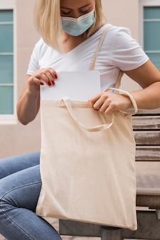 Donna che porta una borsa in tessuto che indossa maschera medica