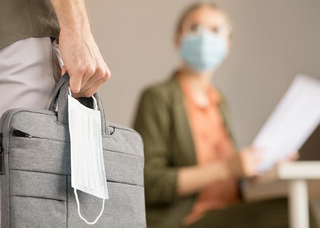 ノートパソコンのバッグとフェイスマスクを運ぶ女性