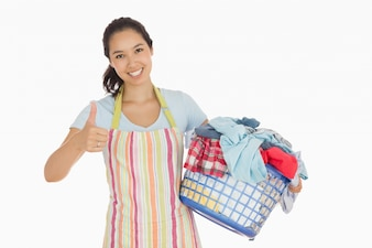 Woman carrying laundry basket and giving thumbs up