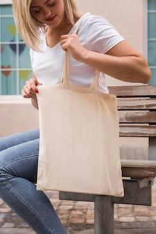 Donna che porta una borsa della spesa e cerca in essa