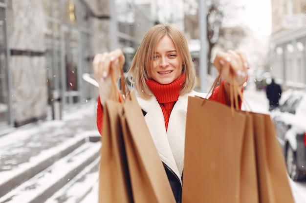 Женщина, несущая хозяйственные сумки в открытом торговом центре