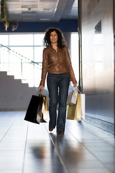 Woman carrying shopping bags in building