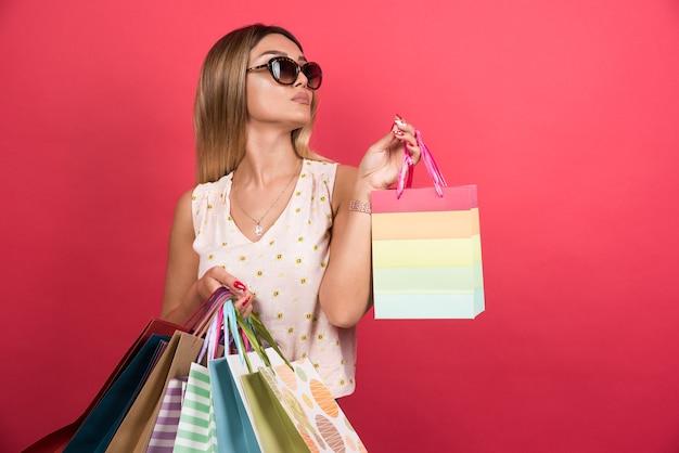 빨간 벽에 쇼핑백을 들고 여자입니다.