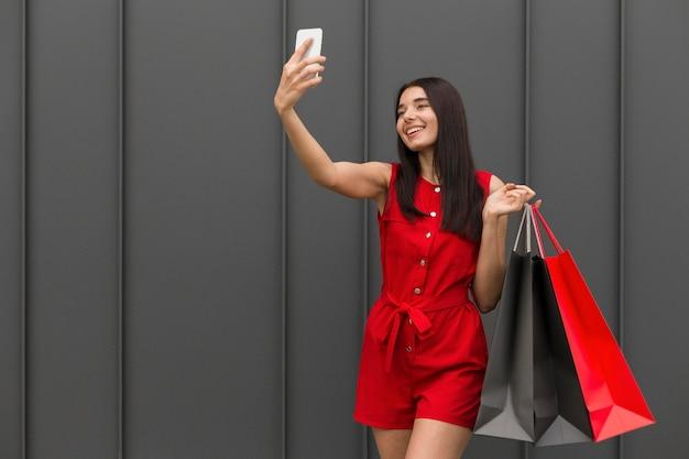 セルフ写真を撮る買い物袋を運ぶ女性