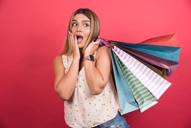 赤い壁に顔を覆いながら買い物袋を運ぶ女性。