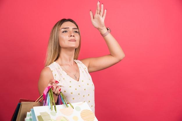 빨간 벽에 찾는 동안 쇼핑 가방을 들고 여자.