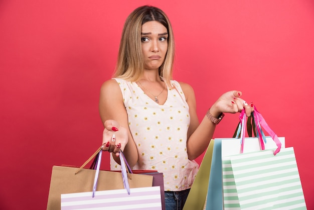 Woman carrying shopping bags with sad expression on red wall .