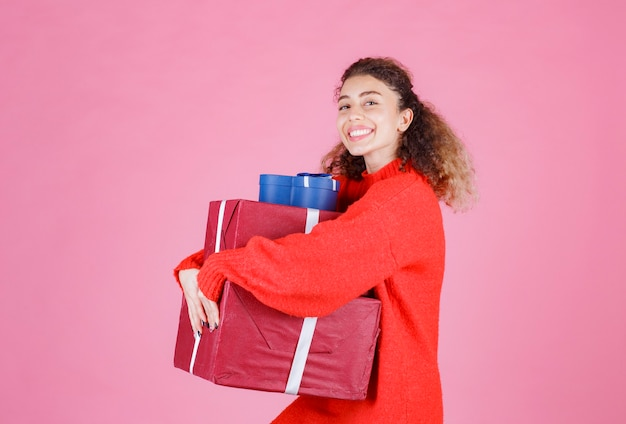 Donna che trasporta una scorta di grandi scatole regalo.