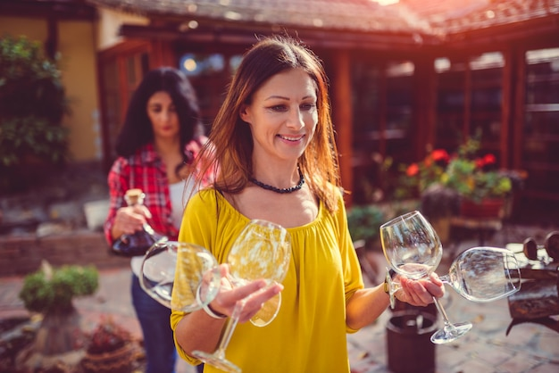 Woman carrying wine glasses at backyard patio