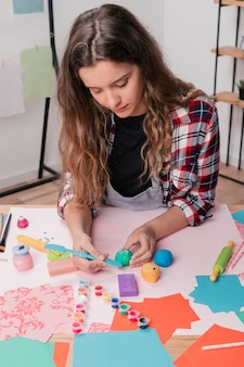 Woman carving colorful clay for making cartoon face