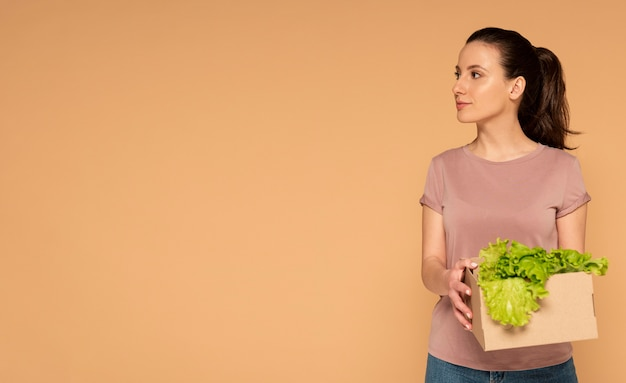 Woman in casual clothes carrying reusable cartoon box with vegetables