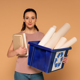 Donna in abiti casual che trasportano riutilizzabili scatola di riciclaggio