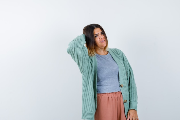 Woman in casual clothes keeping hand behind head and looking confused , front view.