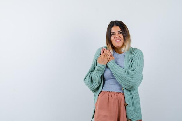 Donna in abiti casual tenendo le mani sul petto e guardando allegra, vista frontale.