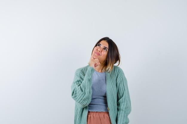Donna in abiti casual appoggiando il mento a portata di mano e guardando sognante, vista frontale.