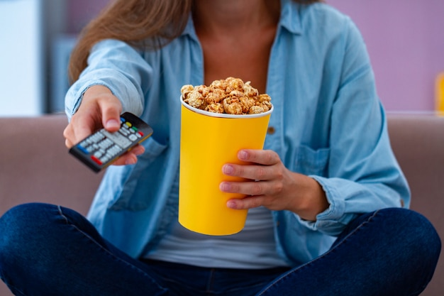 Woman in casual clothes resting and eating crispy caramel popcorn while watching tv