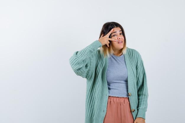 Donna in abiti casual che mostra il segno a v sull'occhio e sembra sicura, vista frontale.