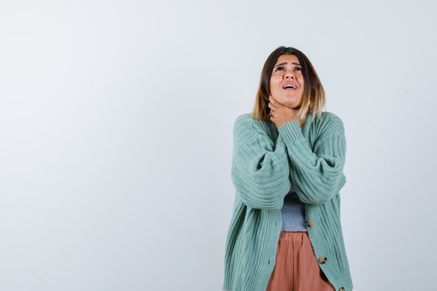 Woman in casual clothes suffering from sore throat and looking painful , front view.