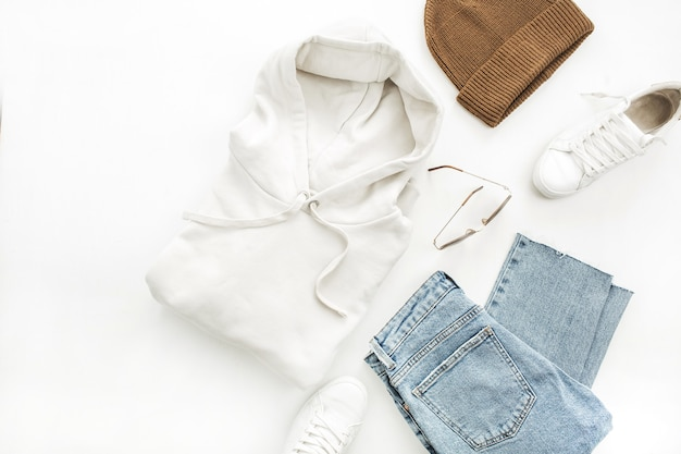 Woman casual fashion clothes and accessory set on white background. hoody, boyfriend jeans, hat, sneakers, sunglasses. flat lay, top view