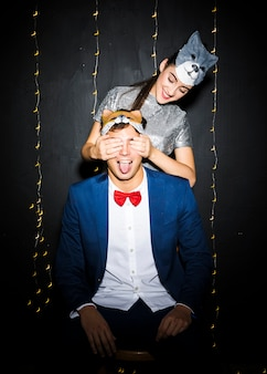 Woman in cat mask closing eyes to man with fox mask and showing tongue