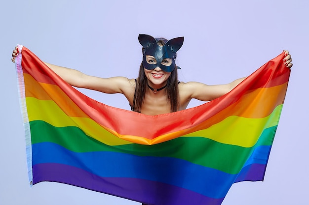 A woman in a cat mask holds a rainbow flag.