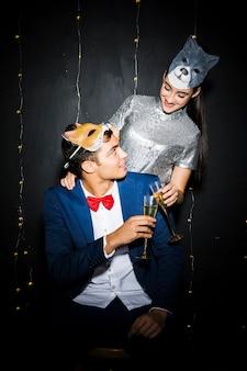 Donna nella mascherina del gatto che abbraccia uomo in maschera di volpe e occhiali aderenti