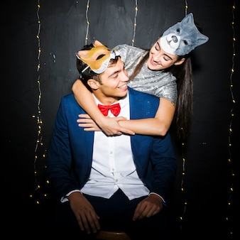 Woman in cat mask hugging man in fox mask