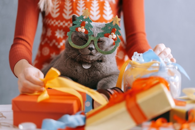 Woman and cat at the table are packing boxes with christmas gifts