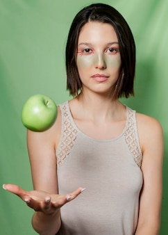 Woman catching apple and posing