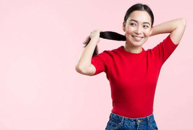 ポニーテールで髪を引く女性